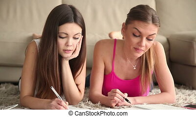 Two beautiful student girls studying at home - Two beautiful...