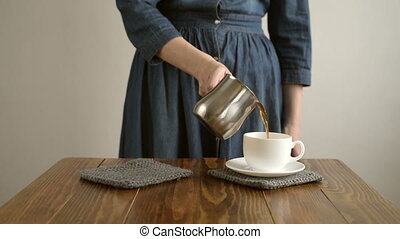 Woman pouring coffee to a cup. Woman is unrecognizable