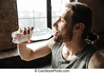 Close up of a healthy young fitness man drinking water from...