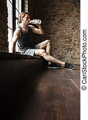 Portrait of a tired sportsman drinking water from a bottle -...