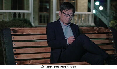 Asian businessman in the night Park uses a smartphone