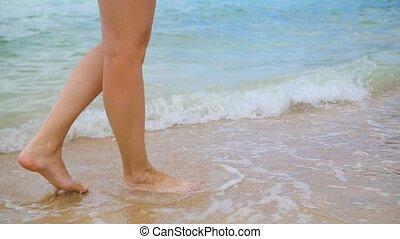 young girl walks along the shore of the beach. Feet closeup
