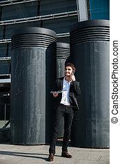 Handsome man talking on phone - Full-length shot of handsome...