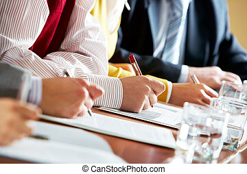 Conference - Close-up of human hands over business documents...