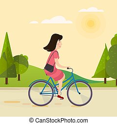 Happy girl riding a bicycle in the park