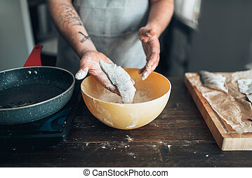 Male chef hands cooking fish on a frying pan. Food cooking....