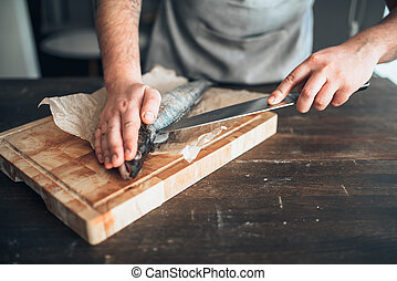 Chef hands with knife cut up fish on cutting board - Male...