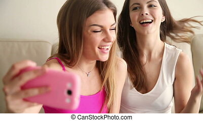 Two happy girlfriends making silly faces on selfie. Friends...