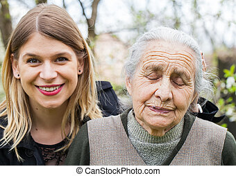 Sick old lady with her joyful carer