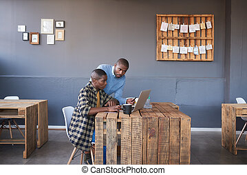 African businessmen working on a laptop together in an...
