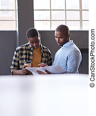African businessmen talking over paperwork together in an office