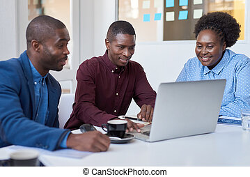 Young African colleagues working on a laptop in an office