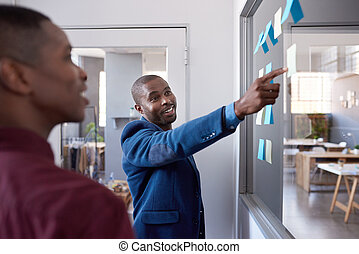 African businessmen strategizing with sticky notes on a...
