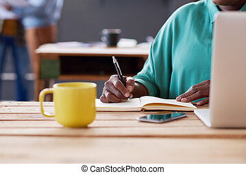 African businesswoman writing notes at her desk in an office...