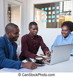 Smiling young African coworkers using a laptop  in an office