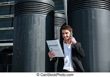 Busy man holding documents and talking on phone - Young busy...