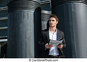 Serious businessman holding documents - Serious handsome...