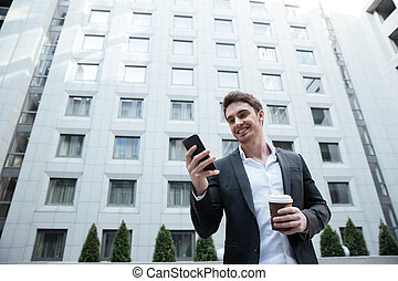 Businessman using smartphone - Smiling businessman with...