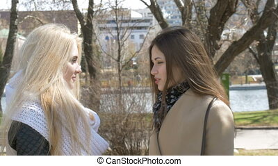 Two beautiful girls, blond and brunette, talking in the...