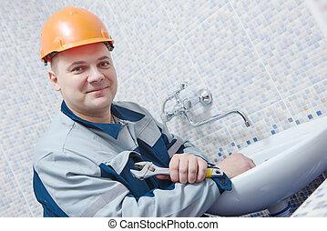 Plumber service. worker installing mixer tap in bathroom