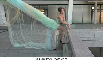 Woman's dress is blowing the wind. - Beautiful girl standing...
