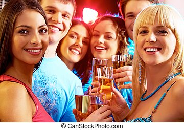 At party - Portrait of happy young people holding glasses of...