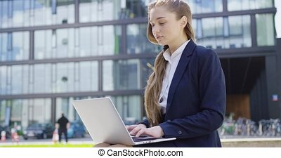 Formal woman with laptop on street - Young woman in formal...