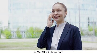 Cheerful girl talking phone on street - Cheerful young woman...