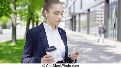 Girl in suit with coffee and smartphone - Beautiful young...