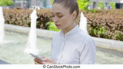 Woman in white shirt using phone - Young concentrated girl...