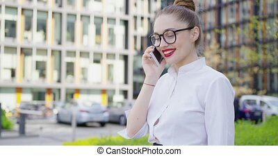 Pretty girl talking phone on street - Pretty young woman...