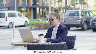 Businesswoman with laptop in outside cafe - Young stylish...