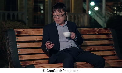 Asian businessman in the night Park uses a smartphone and drinking a Cup of coffee