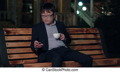 Asian businessman in the night Park uses a smartphone and drinking a Cup of coffee. Smiling