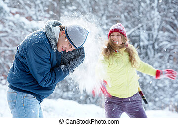 Snow play - Portrait of joyful woman throwing snowball at...