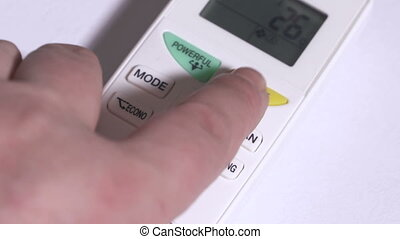 Using air conditioner remote control closeup. Setting an air...