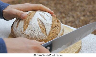 Men's hands cut a loaf of bread. Closeup of hands cutting...