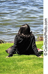 Female relaxing. - Female relaxing by lake outdoors.