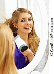 Drying hair - Image of pretty female looking in mirror while...