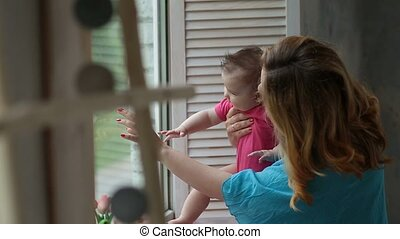 Happy mother with baby girl looking through window - Loving...
