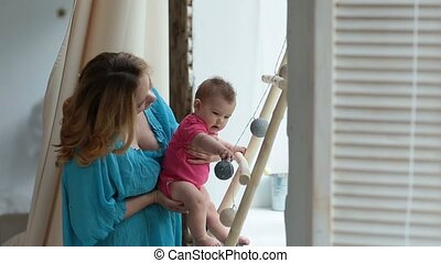 Cheerful mother checking baby's grasping reflex - Attractive...