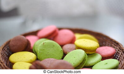 girl puts a yellow macaroons in a bowl on the table close-up