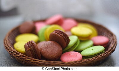 girl pulls out macaroons cookies from the braided baskets...