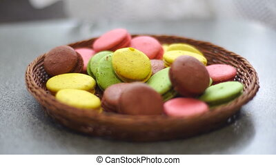on the table there is a basket with bright whickered cookies...