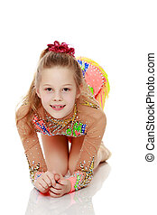 Beautiful girl gymnast sitting on the floor. - Beautiful...
