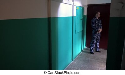 Guard dressed in military uniform guards the apartment.