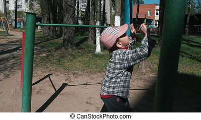 Child plays sports (Playground) - A little boy of 5-6 years...