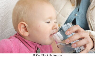 Baby drinking water from glass from mother's hand