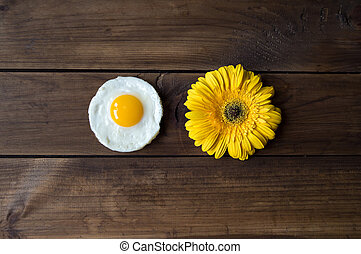 round shaped fried egg with yellow gerbera on dark wooden...