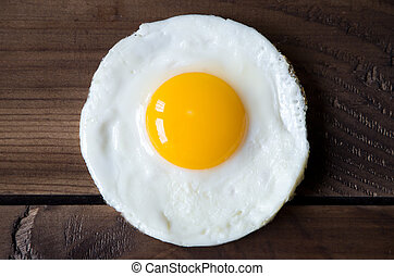 round shaped fried egg for healthy breakfast on dark wooden...